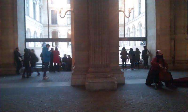 Les visiteurs frustrés se collent à la vitre de la cour Richelieu pour prendre en photo les sculptures.
